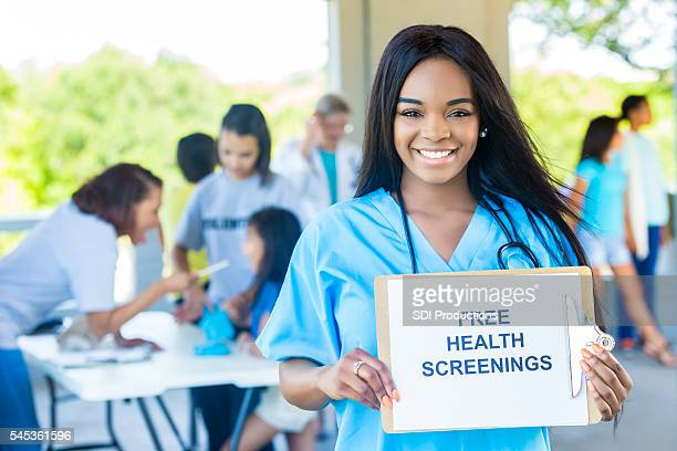 "Beautiful African American Woman holding a """"Free Health Screenings"""" sign"