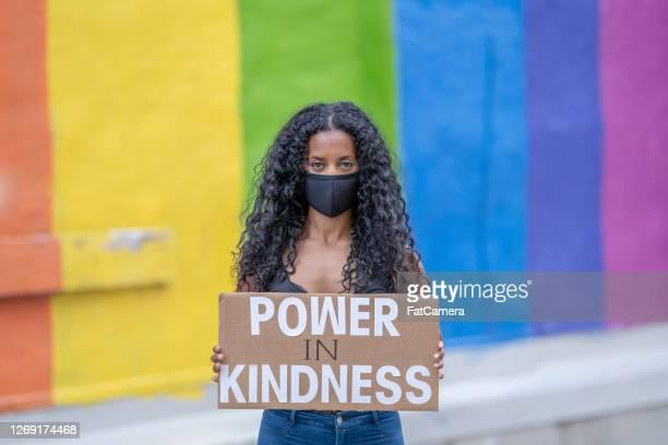 beautiful african american woman holding a protest sign - giustizia sociale foto e immagini stock