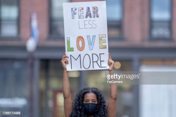 beautiful african american woman holding a protest sign - fatcamera stock pictures, royalty-free photos & images