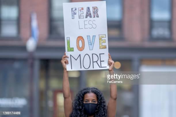 抗議の看板を持つ美しいアフリカ系アメリカ人の女性 - ブラック・ライヴズ・マター ストックフォトと画像