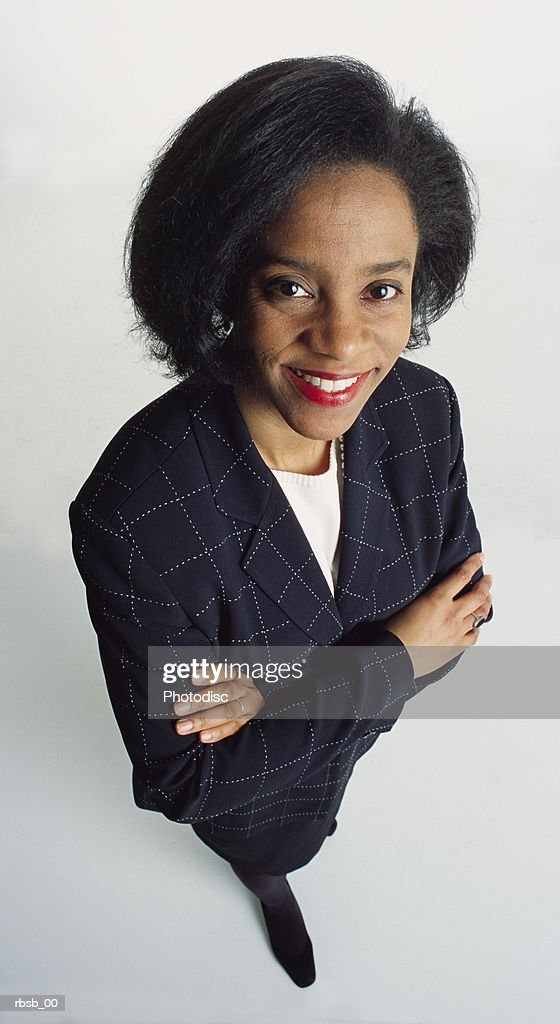 beautiful african american woman in a blue suit smiling and looking up at the camera with her arms crossed : Foto de stock