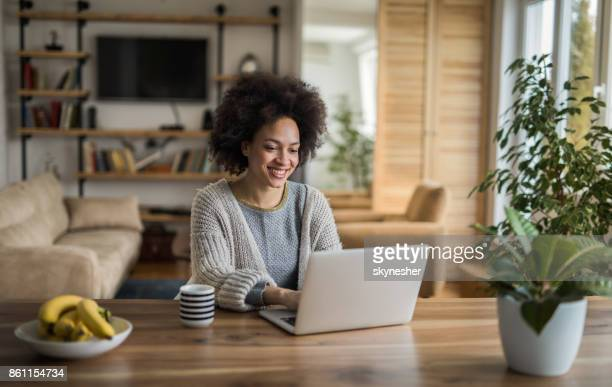 beautiful african american woman typing an e-mail on laptop at home. - using laptop stock pictures, royalty-free photos & images