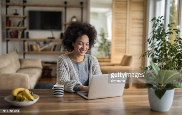 linda mulher afro-americana digitar um e-mail no laptop em casa. - laptop - fotografias e filmes do acervo