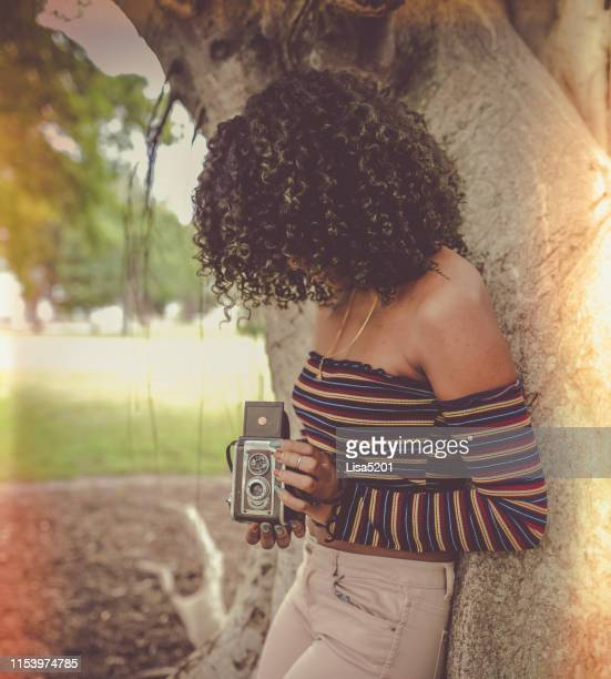 beautiful african american woman with natural hair uses a retro camera in a vintage style image - 1960 stock pictures, royalty-free photos & images