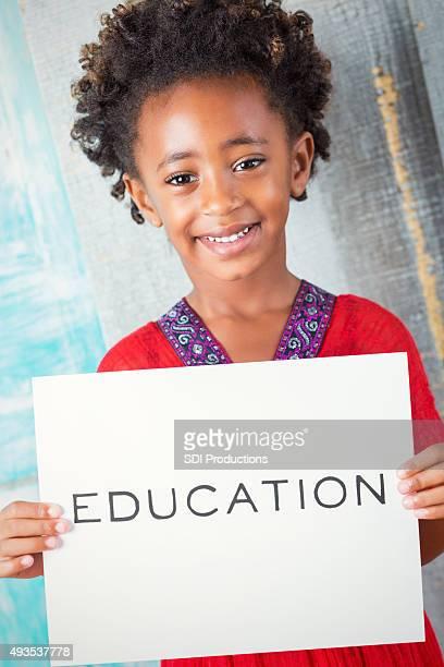 beautiful african child holding education sign - beautiful ethiopian girls stock photos and pictures
