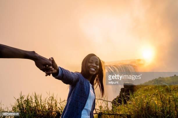 Prachtige Afrikaanse meisje trekken iemand naar Victoria Falls