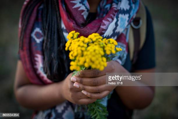 Beautiful african woman holding bouquet of flowers