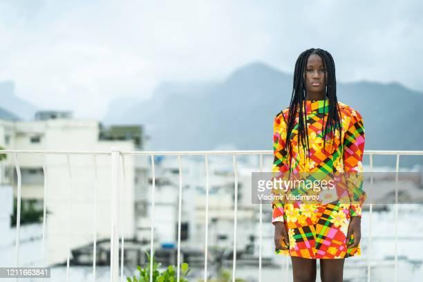 vacker afrikansk kvinna som står på terrassen i traditionell klänning - flerfärgad klänning bildbanksfoton och bilder