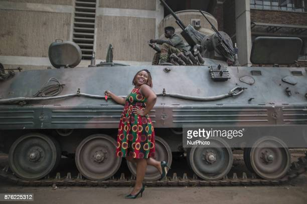 A beautiful African woman takes pictures with one of the armored vehicles in the streets of the capital Harare Zimbabwe on 19 November 2017 a day...