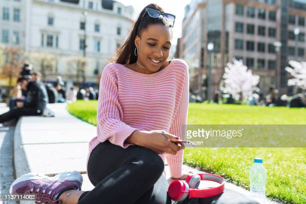 Beautiful African woman with smart phone on sunny springtime day.