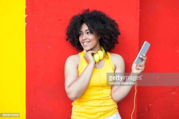 Belle femme africaine avec casque jaune et téléphone intelligent