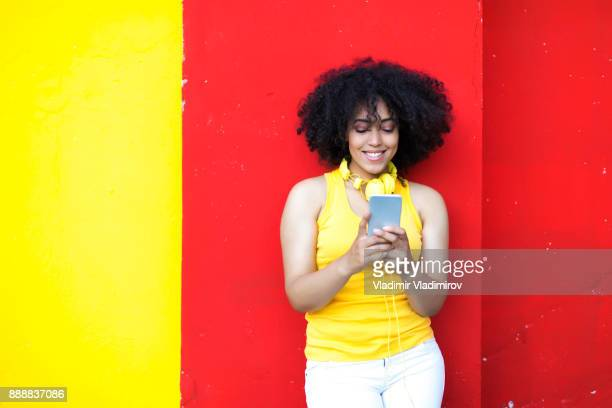 Beautiful african woman with yellow headphones and smart phone