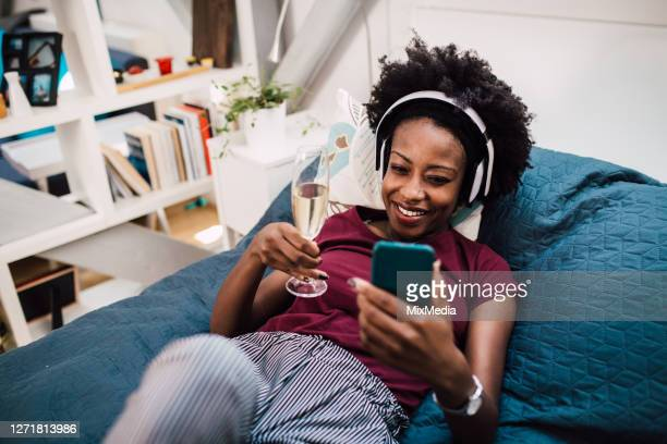 beautiful african-american  woman enjoying in her bed and drinking wine with her online date - flirting stock pictures, royalty-free photos & images