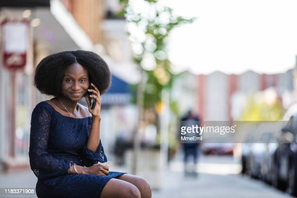 beautiful african-american woman speaking on mobile phone in the street of a small city - mmeemil stock photos and pictures