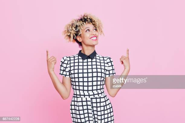 beautiful afro american young woman pointing at copy space - black people laughing stock photos and pictures