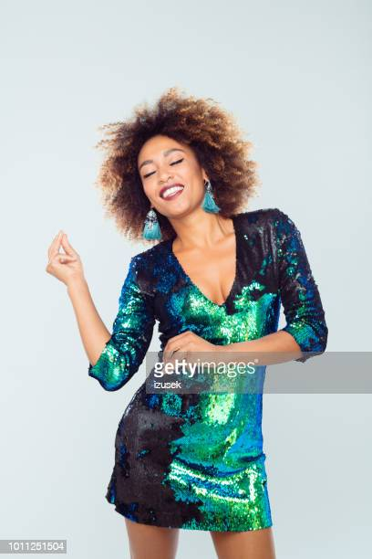 beautiful afro girl dancing in sequined dress - green dress stock pictures, royalty-free photos & images
