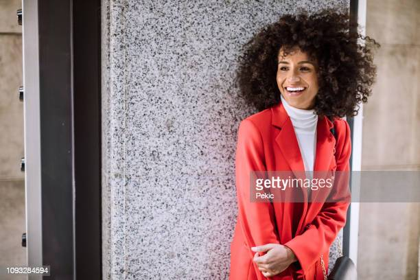 beautiful afro woman in shopping - red coat stock pictures, royalty-free photos & images