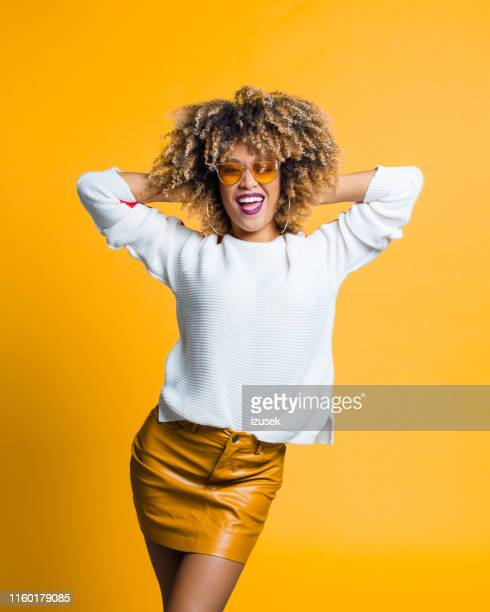 beautiful afro woman posing against yellow background - izusek stock pictures, royalty-free photos & images