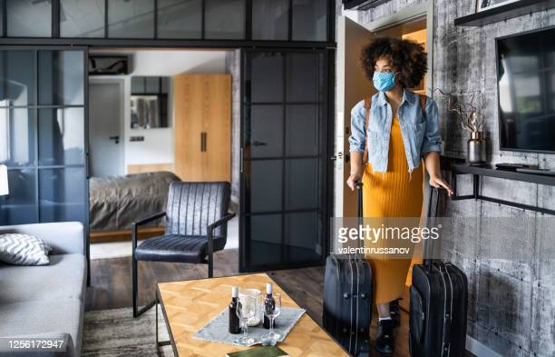 beautiful afro woman with protective face mask arriving in hotel room - hotel stock pictures, royalty-free photos & images