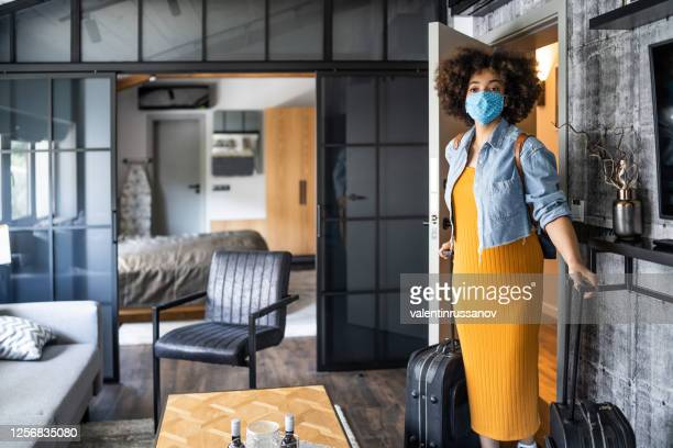 beautiful afro woman with protective face mask arriving in hotel room - guest stock pictures, royalty-free photos & images