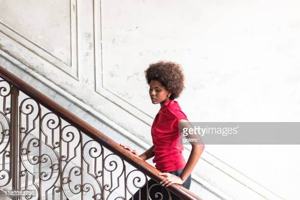 beautiful afro-caribbean woman on stairway in old house in havana - afro caribbean ethnicity stock pictures, royalty-free photos & images