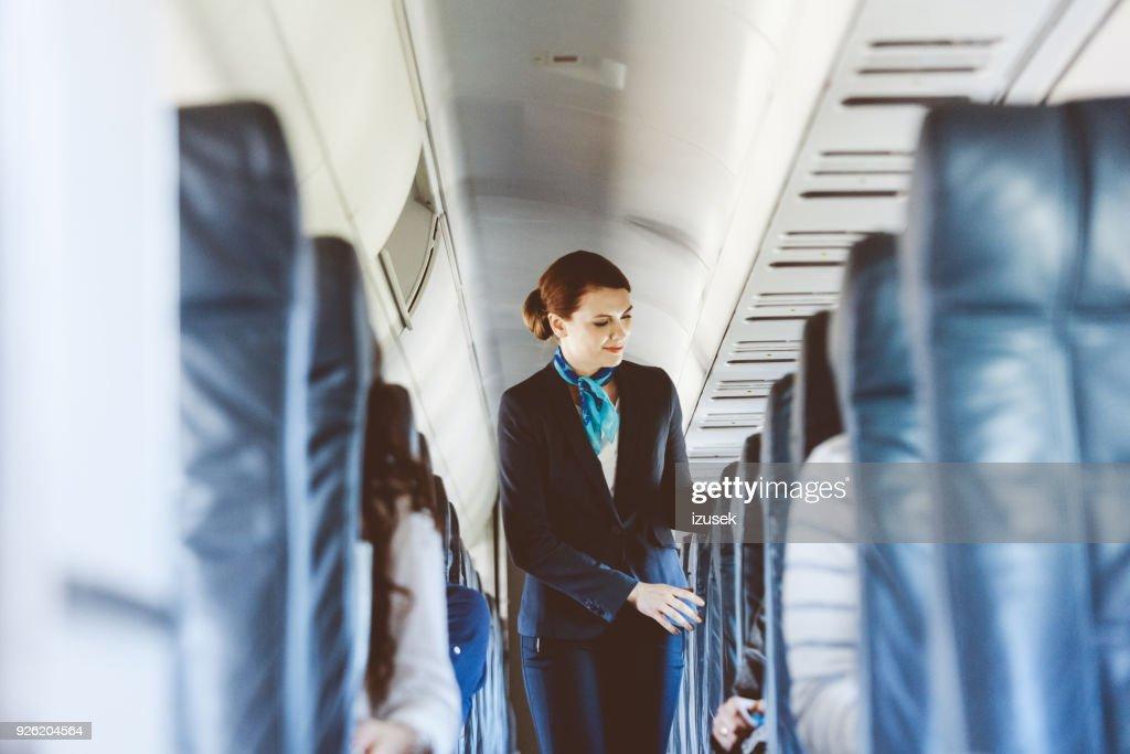 Beautiful air stewardess inside an airplane : Stock Photo