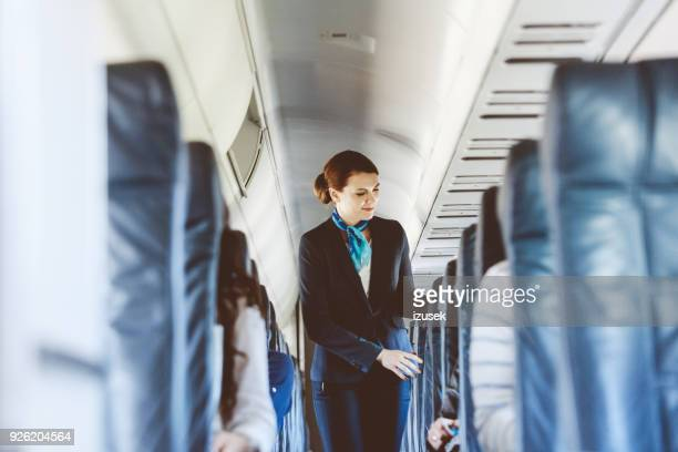 beautiful air stewardess inside an airplane - commercial aircraft stock photos and pictures