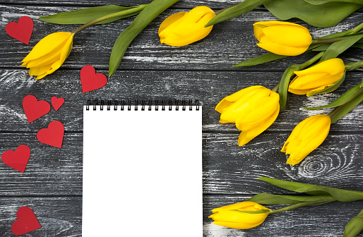 Beautiful and bright bouquet of tulips, red paper hearts scattered all around And a notebook with white sheets lie on a dark vintage wooden table. 928351362