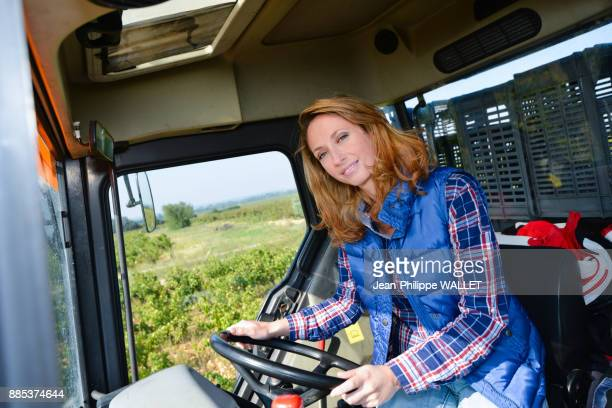 beautiful and cheerful young woman farmer driving tractor in the fields during harvest season in countryside- Cepage Grenache, Chateauneuf du Pape, cotes du Rhone, France