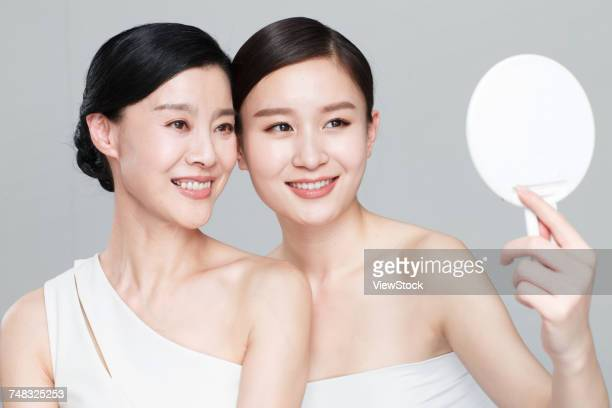 Beautiful and elegant mother and daughter in the mirror