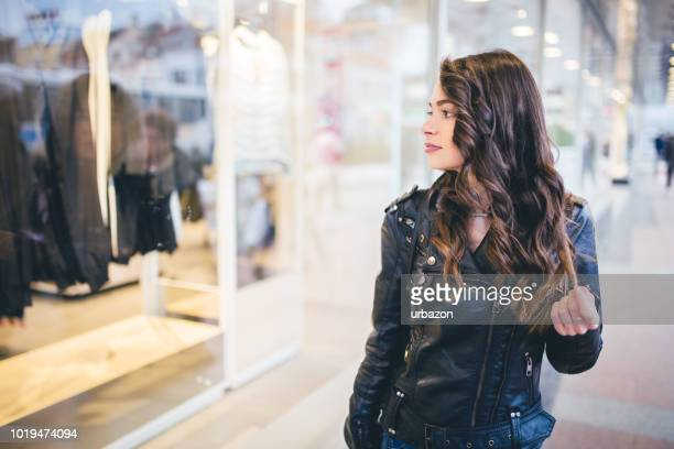 Beautiful and fashionable girl walking the city  and looking at shop windows.