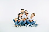 Beautiful and happy smiling young family in white T-shirts are hugging and have a fun time together while sitting on the floor and looking on camera.