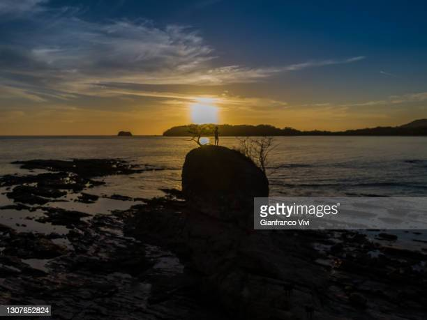 beautiful and peaceful aerial view of a woman practicing yoga and meditation on a rock over the sunset in a beach - playa carrillo fotografías e imágenes de stock