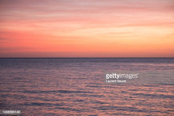 beautiful and romantic warm colored sunset sky on the sea - laurent sauvel photos et images de collection