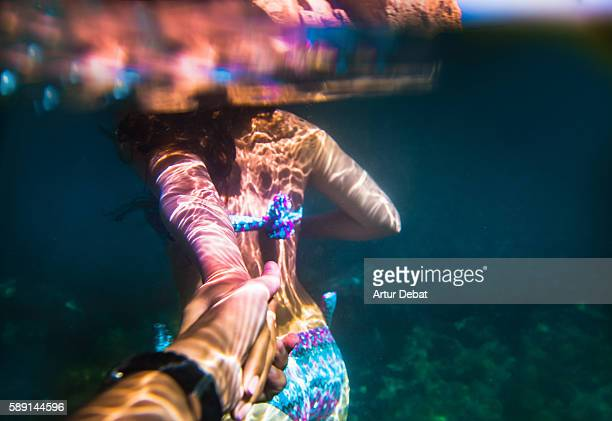 Beautiful and sensual girl lead the way holding hands of a guy taken the picture from personal point of view with underwater view in the Costa Brava during summer vacations.