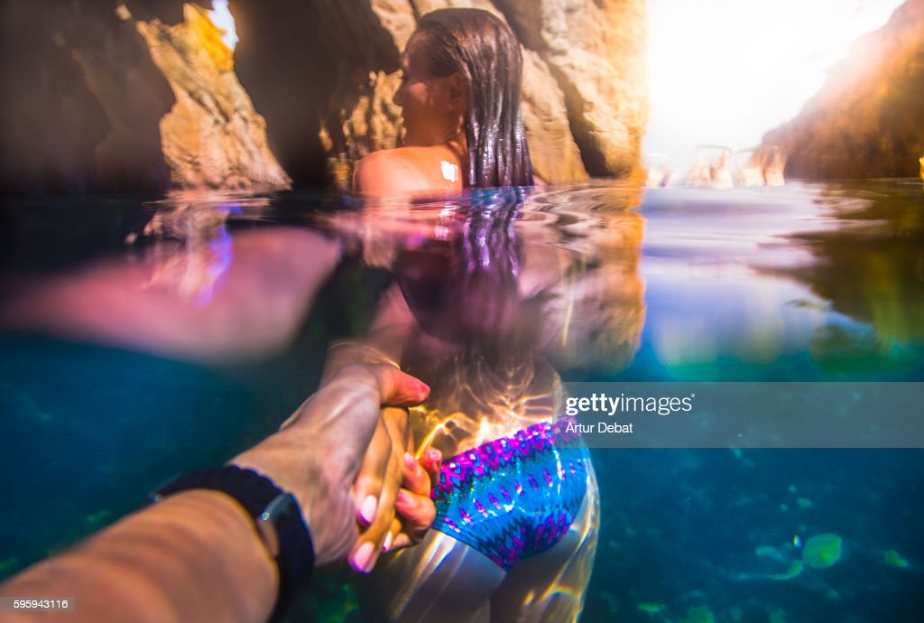 Beautiful and sensual girl lead the way holding hands of a guy taken the picture from personal point of view with underwater view in the Costa Brava during summer vacations. Follow me. : Stock Photo