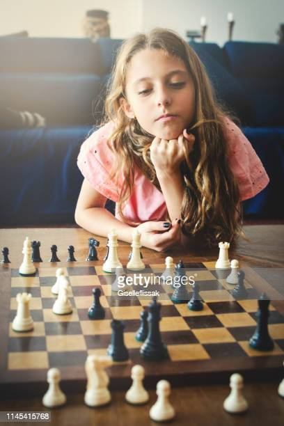 beautiful and smart girl playing chess - playing chess stock pictures, royalty-free photos & images