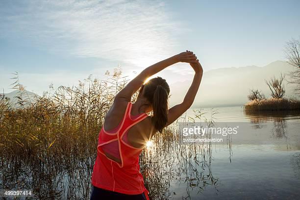 Belle jeune femme sportive et des étirements après piste de jogging en plein air