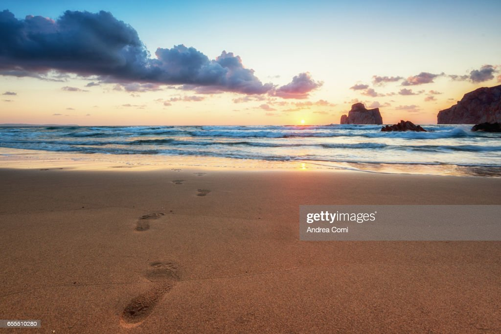 Beautiful and warm sunset with little clouds. Footprints in the sand in the foreground, Pan di Zucchero in the background. Masua beach, Sardinia, Italy, Europe : Stock Photo
