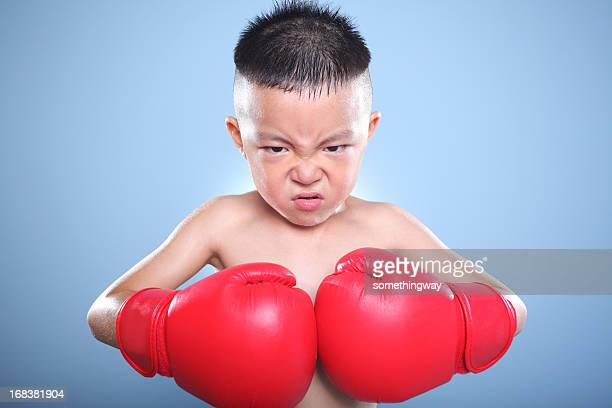 beautiful angry young boy play boxe with gloves