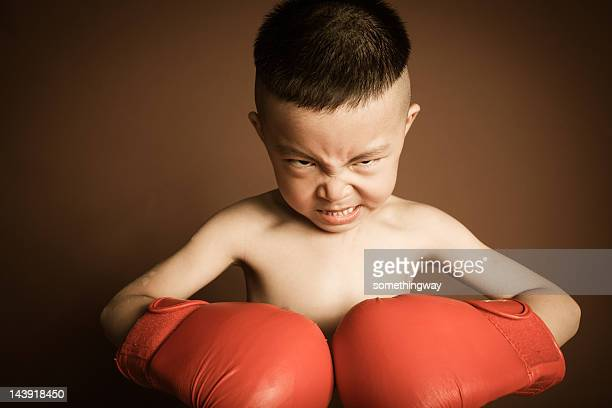beautiful angry young boy play boxing with gloves