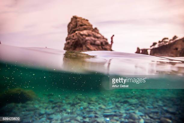 Beautiful aquatic view in the Costa Brava shoreline with underwater nature view and sunset sky between crags on summertime.