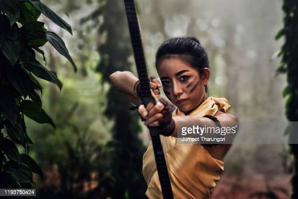 beautiful archer is aiming her longbow to shoot in jungle with beautiful sunlight background - hunting stock pictures, royalty-free photos & images