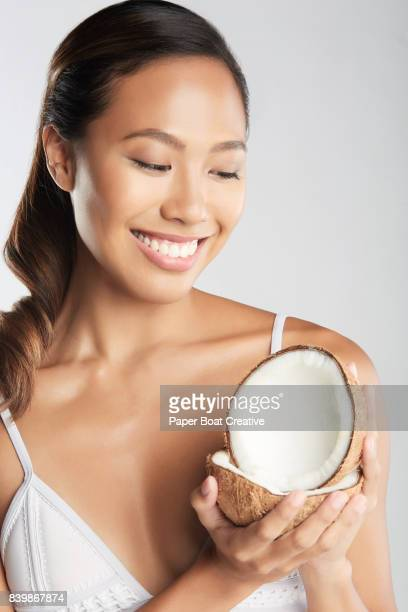 beautiful asian athlete holding a freshly cut coconut educating us the benefits of drink fresh coconut juice - coconut oil stock pictures, royalty-free photos & images
