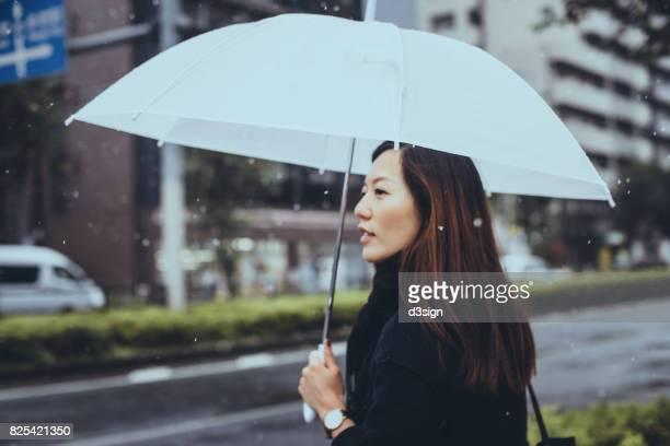 Beautiful Asian businesswoman holding umbrella walking in the city street