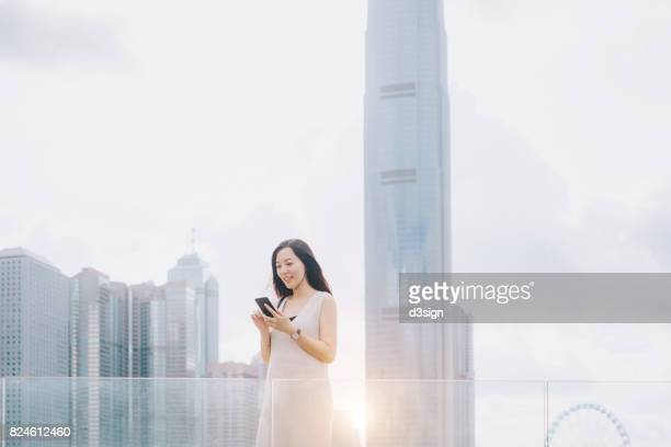 Beautiful Asian businesswoman using smartphone on urban balcony against highrise financial skyscrapers in city