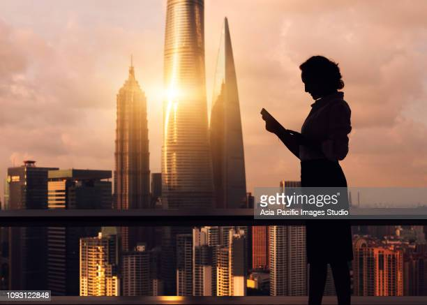 Beautiful Asian businesswoman working near the window, the background is skyscrapers and landmarks of Shanghai, including Shanghai Tower, Shanghai World Financial Center and Jin Mao Tower.