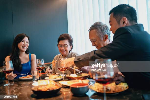 beautiful asian family enjoying a meal in a restaurant - singapore stock pictures, royalty-free photos & images