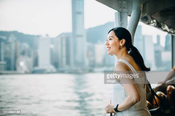 beautiful asian female traveller enjoying the iconic city view of hong kong and victoria harbour while riding on star ferry - fähre stock-fotos und bilder