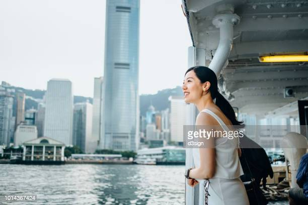 beautiful asian female traveller enjoying the iconic city view of hong kong and victoria harbour while riding on star ferry - international landmark stock pictures, royalty-free photos & images